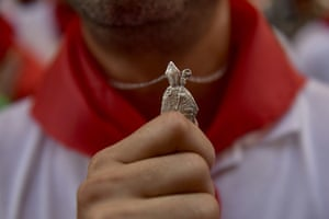 A man holds a necklace of Saint Fermín before the first running of the bulls