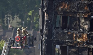 Firefighters inspect the fire damage to the Grenfell Tower block