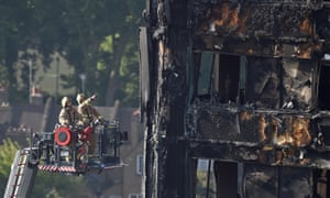 Firefighters inspect the Grenfell Tower block in north Kensington, west London.