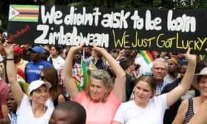 Protesters carrying pro-Zimbabwe signs