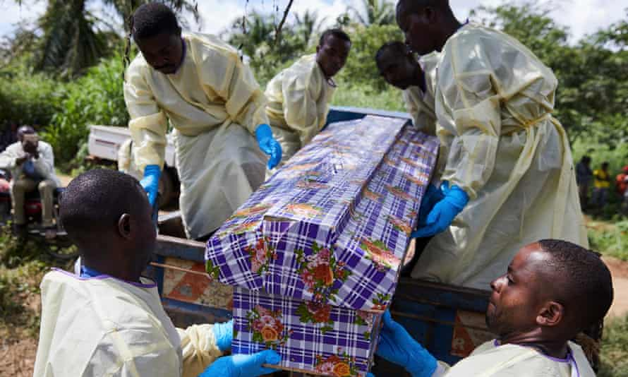 Health workers lift a coffin carrying Kahumbu Ngalyakuthi, who was infected after sharing a hospital room with a patient with Ebola in North Kivu.