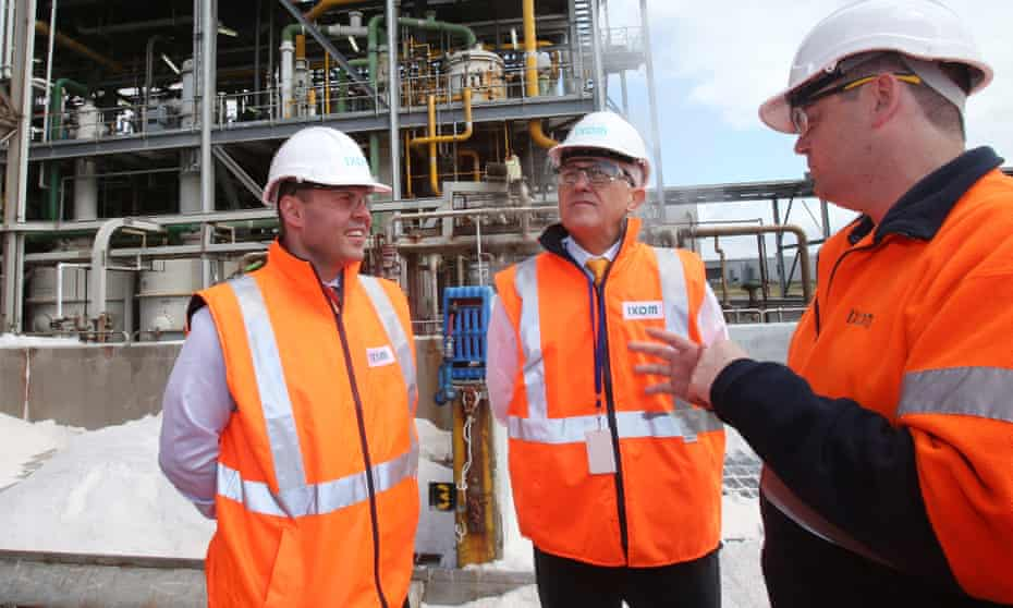 Prime Minister Malcolm Turnbull (centre) and Australian Minister for Energy and the Environment Josh Frydenberg (left) speak to a worker at a plant in Melbourne.