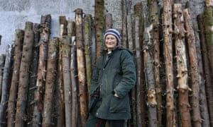 Sioned Jones standing in front of a row of felled Sitka spruce trees leaning against a wall