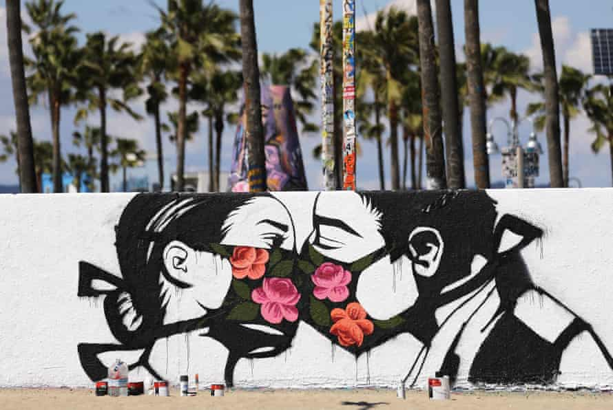 Palm trees stand behind a street art piece by artist Pony Wave depicting two people kissing while wearing face masks on Venice Beach on 21 March 2020 in Venice, California