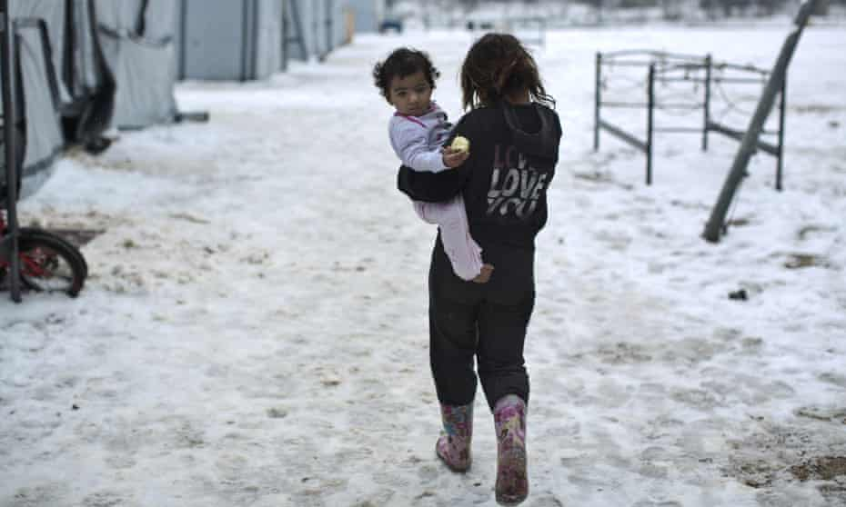 A Syrian refugee girl holds her younger sister while walking back to their shelter at a refugee camp in Athens earlier this year.