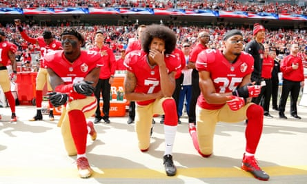 Colin Kaepernick, flanked by Eli Harold and Eric Reid, takes a knee