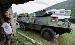A boy looks at a Colombian Army armoured vehicle in Cauca on Wednesday.