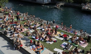 People enjoy hot summer weather on the banks of the Limmat river in Zurich, Switzerland on 27 June 2020, as the spread of coronavirus continues.