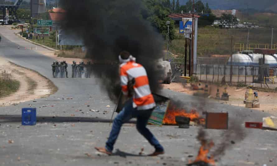 A man stands in front of Venezuelan national guard members, seen from Pacaraima, Brazil.