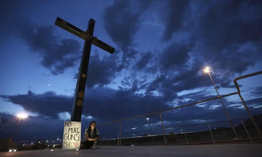 A woman sits under a cross with an anti-guns sign