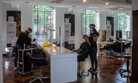 Hairdressers, protected by face masks and shields, at work in Milan, Lombardy, on 18 May 2020. Italy eased some lockdown restrictions on 4 May.
