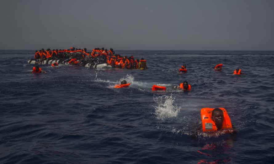 African migrants try to reach a rescue boat in the Mediterranean Sea, about 12 miles north of Sabratha, Libya, on 23 July 2017.