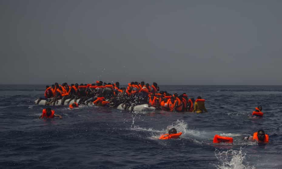 African migrants fall from a punctured rubber boat in the Mediterranean north of Libya.