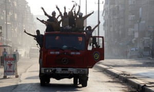 Syrian civil defence volunteers celebrate in Aleppo after the breaking of a three-week government siege.