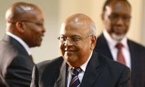 Pravin Gordhan smiling as he walks past Jacob Zuma.