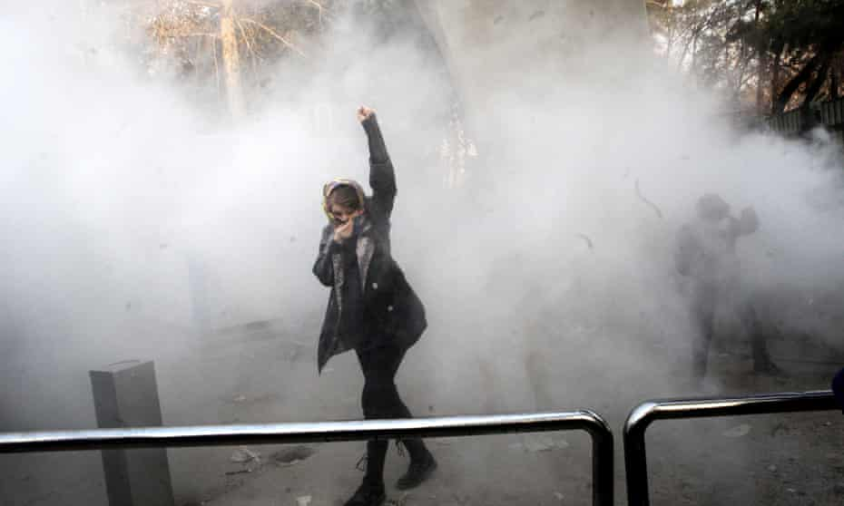 A woman raises her fist as Iranian students clash with riot police during anti-government protests
