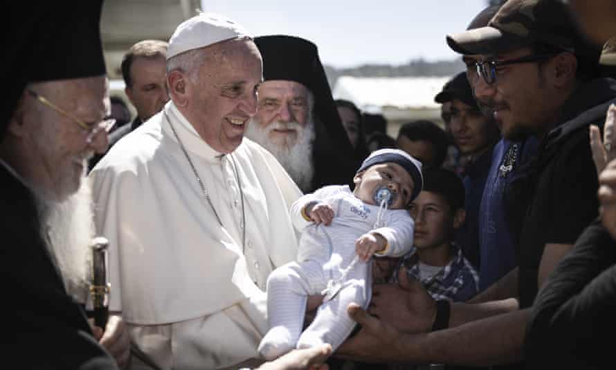 Pope Francis holds a baby at a migration centre in Lesbos