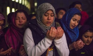 Friends and family members pray at a vigil for Deah Shaddy Barakat, Yusor Mohammad Abu-Salha and Razan Mohammad Abu-Salha, on the campus of North Carolina State University in Raleigh.