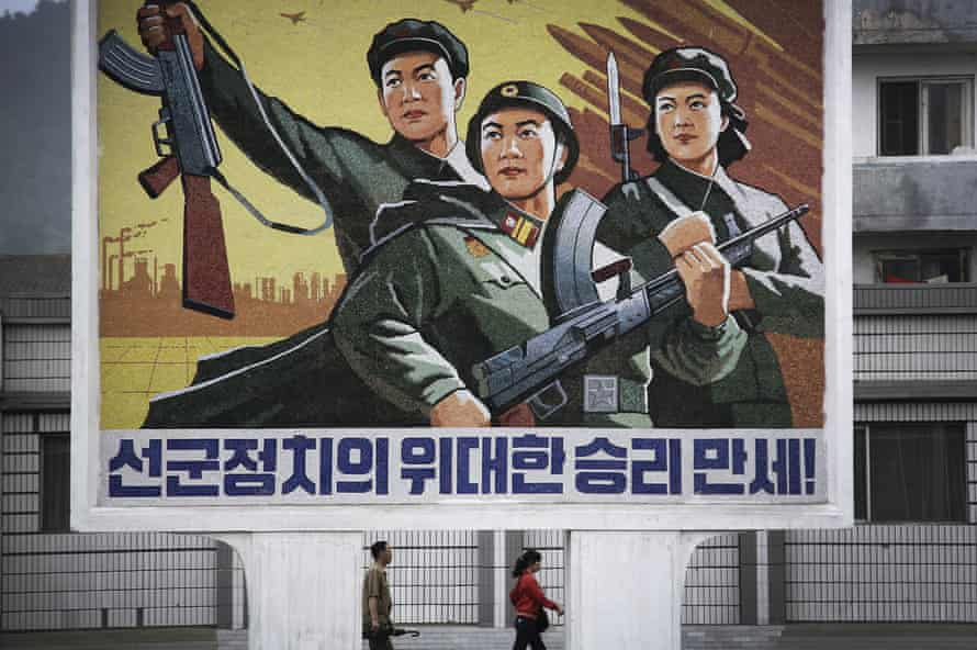 North Koreans pass a mural in Wonsan celebrating Songun, the 'military-first' policy that allocates resources to the armed forces.