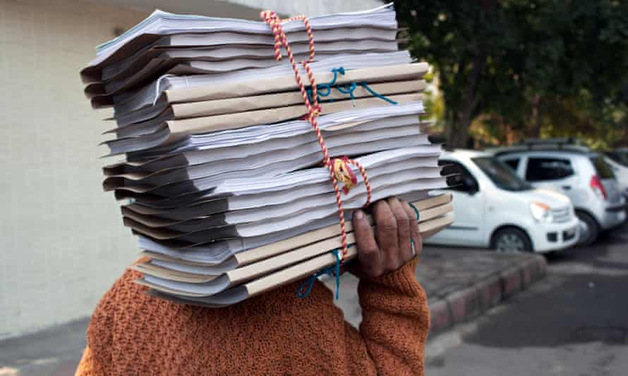 A man carries a pile of documents outside one of the courts in New Delhi, India.
