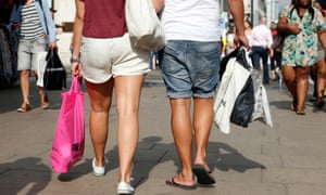 Shoppers in shorts and sandals stroll through the high street