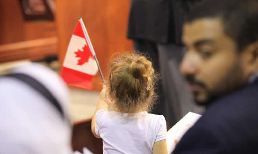 A little girl raising national flag in a Canadian citizenship ceremony in Kitchener, Ontario.