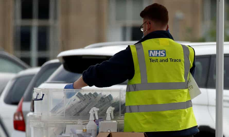An NHS test and trace worker sorts through coronavirus tests at a drive-through facility in Bolton.