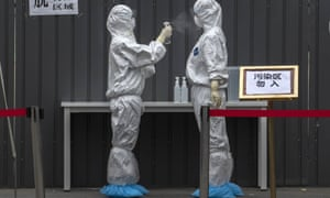 Chinese epidemic control workers wear protective suits as they disinfect each other after performing nucleic acid swab test for Covid-19 on citizens at a government testing site in Xicheng District during an organised tour on 24 June 2020 in Beijing, China.