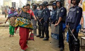 Police stand guard in front of a garments factory in Ashulia