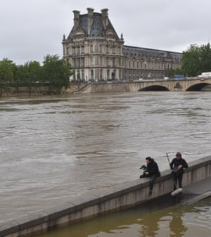 Two photographers take pictures of the Louvre Museum on the other side of the river Seine in Paris.