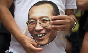 A protester holds a mask of Chinese dissident and Nobel laureate Liu Xiaobo during a protest outside the China Liaison Office in Hong Kong.