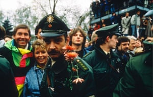 A German policeman with flowers on his uniform mingles with the celebrating crowds