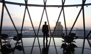 A businessman stands with his briefcase at the top of the Gherkin skyscraper in London