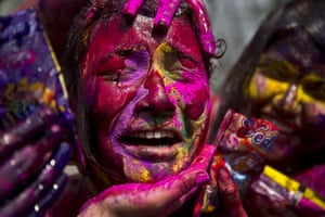 An Indian girl grimaces as her face is smeared with coloured powder during celebrations in Gauhti marking Holi, the Hindu festival of colours