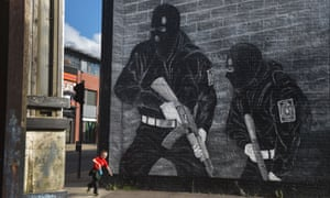 A boy runs past a mural of loyalist paramilitaries in Belfast