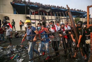 Protesters carry a metal fence panel during clashes with security forces in Baghdad, Iraq