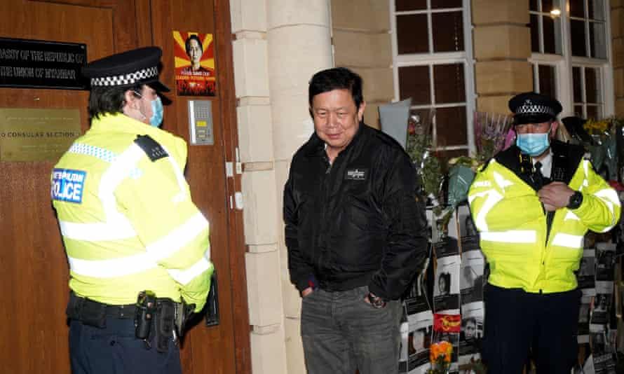 کیاو زوار مین در کنار افسران پلیس در انتظار ورود به سفارت ایستاده است.