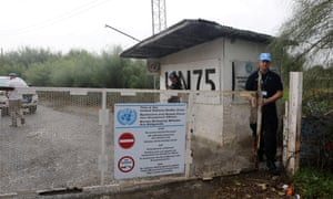 A UN soldier opens a gate leading into the buffer zone in Cyprus