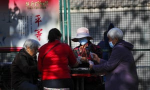 People, some wearing face masks to help curb the spread of the coronavirus, play cards at a park in Beijing, Tuesday, 10 November, 2020.