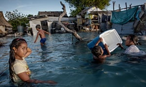 Children play amid flooded homes in Kiribati, now under threat from rising sea levels