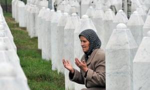 Bida Smajlovic, a survivor of the massacre in Srebrenica, prays by her husband's grave