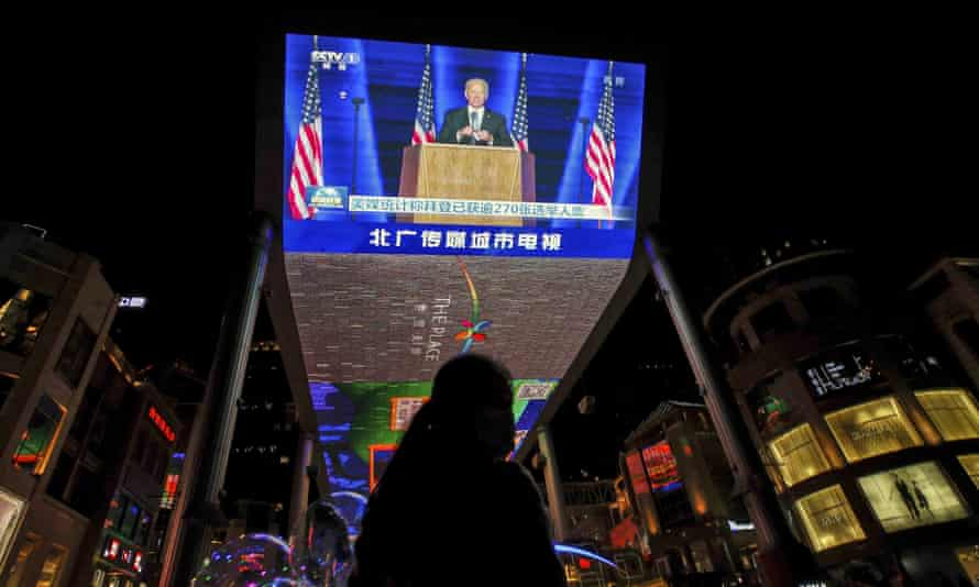 Joe Biden speaks after being elected president of the US, broadcast on a giant TV at a shopping mall in Beijing.