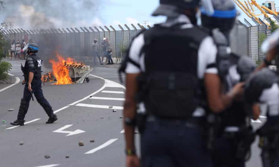 Police officers face demonstrators as people protest against the arrival of the passengers of the Sun Princess cruise ship on the Indian Ocean island of La Reunion without having their temperature checked.