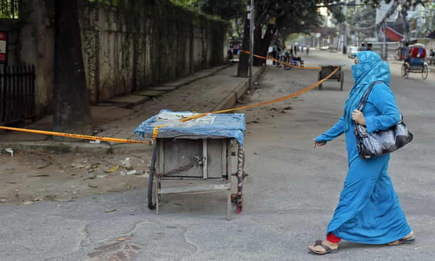 A woman walks past the site where the Italian man Cesare Tavella was shot dead in Dhaka.