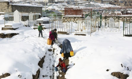 A woman and her children carry containers of water in the snow outside Kabul in Afghanistan after heavy snow.
