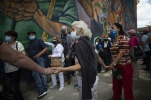 Elderly persons hold hands to avoid others from cutting into the line as they wait outside the Alba Caracas hotel to be vaccinated during a massive vaccination campaign for seniors in Caracas.