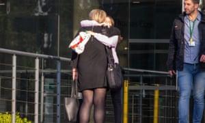 Employees hug outside a Thomas Cook branch.