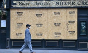 A man passes a boarded-up pub in London.