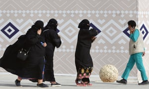 Three women in burqas and a man holding a mobile phone to his ear in Rumah, Saudi Arabia