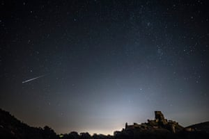 A Perseid meteor flashes across the night sky over Corfe Castle in Dorset, UK